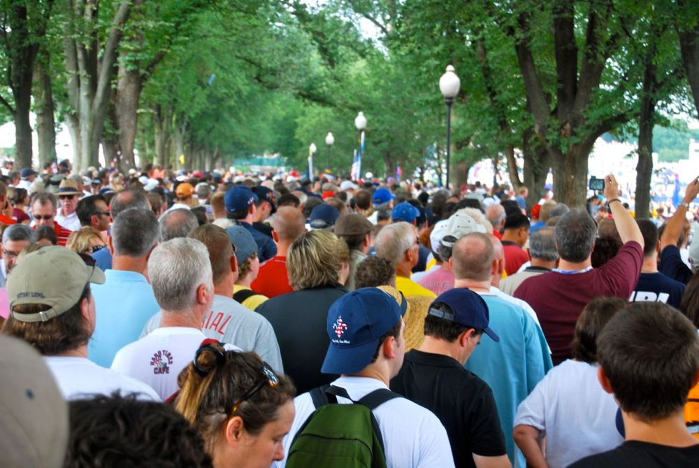 The crowd in the tree line near the reflecting pool